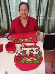 One of the proud women of the sewing program displaying her finished projects.