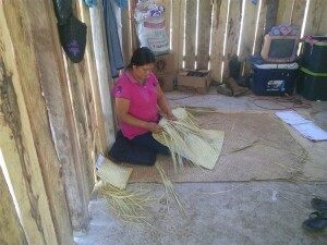 A Pame sister weaving palm leaves into bags which she will sell in the market in order to bring in some household income.