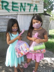 Young girls receive a gift of school supplies from the Hidden Manna Children's ministry. Even in these little squatter villages the fear of the Covid-19 virus keeps even little children masked.