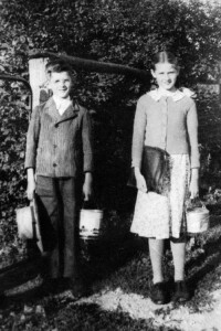 My mother, Lydian and her little brother Amos on their way to school. Notice the honey pails that were thier lunch buckets for school. Mom's seems a tad beat up. Maybe she was beating on too many of the boys with it?
