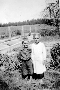 """My mother and her little brother, my uncle Amos Martin in front of their garden on the family farm """"between """"Hawkesville and Saint Clements"""" in southern Ontario"""